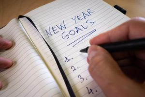 person writing a list of new year's resolutions